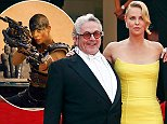 """South African-US actress Charlize Theron (L) and Australian director George Miller leave the Festival palace after the the screening of the film """"Mad Max : Fury Road"""" during the 68th Cannes Film Festival in Cannes, southeastern France, on May 14, 2015.   AFP PHOTO / ANNE-CHRISTINE POUJOULATANNE-CHRISTINE POUJOULAT/AFP/Getty Images"""