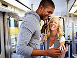 A stock photo of a young couple on subway looking at cell phone.