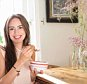 A stock photo of a woman pictured while eating her breakfast.    Smiling woman eating breakfast