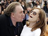 Actor Gerard Depardieu, left, tries to kiss actress Isabelle Huppert during a photo call for the film Valley of Love, at the 68th international film festival, Cannes, southern France, Friday, May 22, 2015. (AP Photo/Thibault Camus)