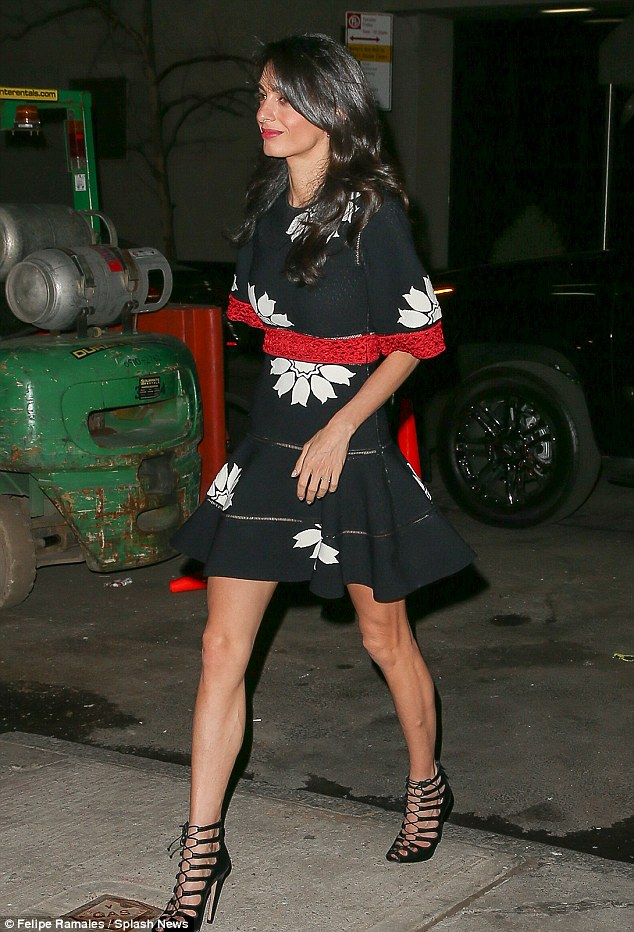The Lebanese-British lawyer flaunted her legs in a black mini dress and lace-up heels