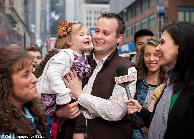 Family: Josh Duggar stands beside his mother (far left) as he and his daughter are interviewed on 'Extra'