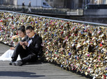 FILE - This Wednesday April 16, 2014 file photo shows a newly wed couple resting on the Pont des Arts in Paris, France. Any hope that the love locks that cling to Paris¿ famed Pont des Arts bridge would last forever _ will be unromantically dashed by the city council who plan to dismantle them Monday _ for good. (AP Photo/Remy de la Mauviniere, File)