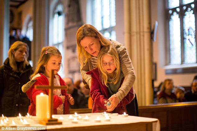 Mourners lit candles for those who had died at a service at the nearby All Saints Church today. Pictured:Kate Thomas helps her daughters Isabel, seven, and Chloe, five