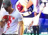 """In this photo provided by Francis Ramsden, Enrique Iglesias grabs a drone onstage during a concert in Tijuana, Mexico on Saturday, May 30, 2015. A representative for the singer says in a statement to The Associated Press that Iglesias was """"semi-treated"""" offstage after his fingers were sliced when he grabbed the drone. During live shows, Iglesias sometimes grabs a drone to show the audience a """"point of view"""" angle. (Francis Ramsden via AP)"""