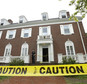 A Tufts University law enforcement official stands behind caution tape outside the Delta Tau Delta fraternity house, in Somerville, Mass., Sunday, May 31, 2015, near the Tufts University, Medford, Mass., campus. Two people were stabbed at the fraternity house early Sunday, leading the school to briefly issue a shelter-in-place order as police searched the campus for a suspect or suspects. (AP Photo/Steven Senne)