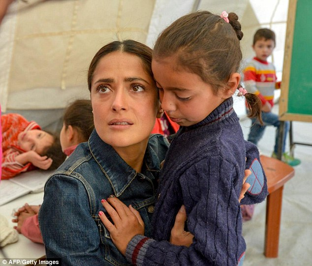 Sad: Salma looked visibly upset as she hugged a young child and a baby during her visit