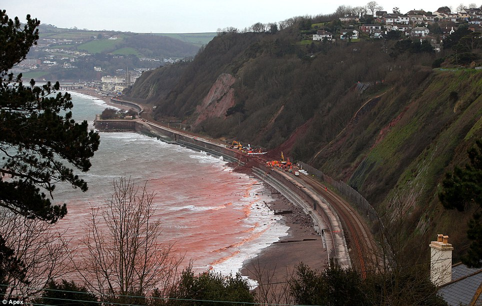 A deliberate landslip at a beach in Devon has turned the sea red after tonnes of earth and stone are thought to have fallen