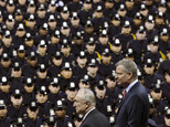 FILE - In this Dec. 29, 2014 file photo, New York City Mayor Bill de Blasio, right, and NYPD police commissioner Bill Bratton, center, stand on stage during a New York Police Academy graduation ceremony at Madison Square Garden in New York. Mayor de Blasio has spent much of the week answering questions about a 9 percent spike in crime in New York. But experts say that a major rise in crime, which hasn't happened yet during his administration, would be more damaging to him than other mayors since he had a reputation for being soft on crime, his relationship with the police is tenuous and so much of his plan to change the justice system is hinged on the idea that crime will not rise. (AP Photo/John Minchillo, File)