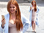 UK CLIENTS MUST CREDIT: AKM-GSI ONLY EXCLUSIVE: **SHOT ON 6/3/15** Isla Fisher dons a cream colored form fitting dress underneath a blue bathrobe while taking a break on the set of her new film, 'Keeping Up with the Joneses' with co-star Jon Hamm. The mom of three who just gave birth in March to latest addition to the family, Montgomery, looked to be back in top form again, looking svelte in her dress. Isla appeared to be face timing her family back home, presumably husband Sacha Baron Cohen and their children back home.  Pictured: Isla Fisher Ref: SPL1046400  050615   EXCLUSIVE Picture by: AKM-GSI / Splash News