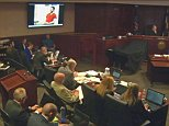 Defendant James Holmes appears in a video presented to a darkened courtroom in Centennial, Colo., Thursday, June 4, 2015. Holmes, also seated at defense table below screen, spoke in the video to a psychiatrist who evaluated him for the trial on charges that he killed 12 people and wounded 70 others during the midnight premiere of a Batman film. (Colorado Judicial Department via AP, Pool)