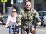 UK CLIENTS MUST CREDIT: AKM-GSI ONLY EXCLUSIVE: Former California Governor and actor Arnold Schwarzenegger and his girlfriend enjoy a beautiful day in Santa Monica by biking around town.  Arnold wore a camouflaged jacket with matching slip ons, while his girlfriend trailed behind him in a white t-shirt and navy blue cropped leggings.  Pictured: Arnold Schwartzenegger Ref: SPL1048110  070615   EXCLUSIVE Picture by: AKM-GSI / Splash News