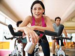 A woman in a spinning class on an exercycle in a gym / health club.