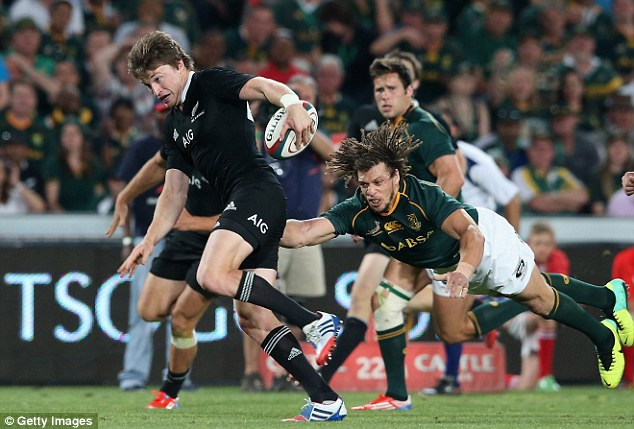 On his way: Beuden Barrett slips a tackle to run in another try for the All Blacks