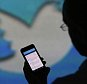 A user checks a Twitter feed on the screen of an Apple Inc. iPhone 5 smartphone in this arranged photograph taken in London, U.K., on Friday, Oct. 4, 2013. Twitter Inc.'s initial public offering documents suggested a valuation of $12.8 billion for the microblogging service, underscoring the seven-year rise of a still unprofitable company that has helped revolutionize how people share information. Photographer: Chris Ratcliffe/Bloomberg via Getty Images