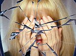 A woman covers her face reflected in a  broken mirror or the shattered life concept; Shutterstock ID 141673471
