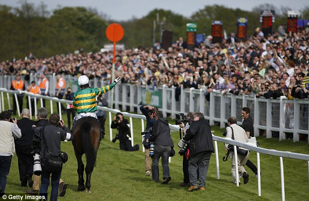 McCoy waves goodbye to the fans who line the fence and pack the racecourse to see his final ride