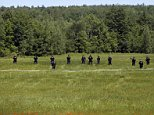 Law enforcement officers walk in a field along Route 3 on Saturday, June 13, 2015, in Saranac, N.Y. Hundreds of law enforcement personnel have begun an eighth day searching for David Sweat and Richard Matt, two killers who used power tools to cut their way out of Clinton Correctional Facility in Dannemora in northern New York. (AP Photo/Mike Groll)