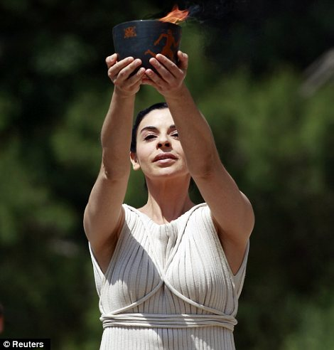 Greek actress Ino Menegaki, playing the role of High Priestess, holds up the cauldron