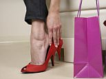 Woman trying on red shoes --- Image by © Stuart O'Sullivan/Corbis