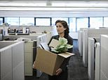Young businesswoman carrying cardboard box containing personal items and pot plant in open-plan office. REDUNDANCY / WOMEN /