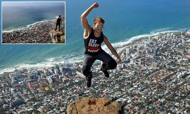 Tourist snapped jumping into the air on edge of Lions Head in South Africa