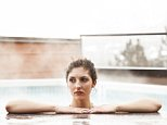 A stock photo of beautiful woman in steaming outdoor pool on winter day.