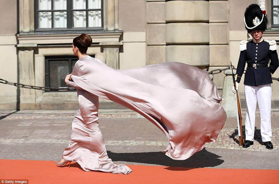 The train of a guest's dress blows in the wind as she waltzes down the red carpet en route to the royal wedding this afternoon