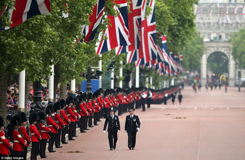 Policemen in their dress uniforms walk past lines of soldiers along The Mall as they prepare for the Queen to be taken past as part of her official birthday celebrations