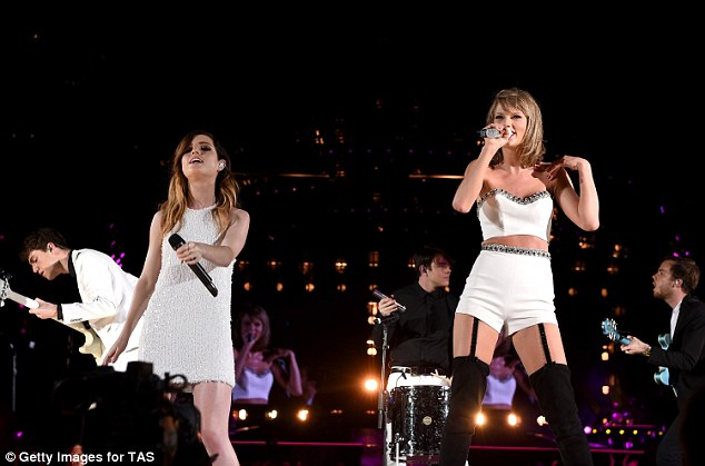 Wonder in white: One of Taylor's raciest looks was a matching strapless crop top and tiny high-waisted shorts combination complete with black suspenders attatched to black stockings