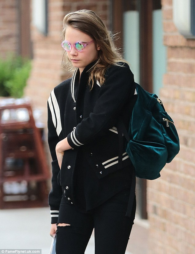 Low-key: Wearing a pair of ripped jeans with a black baseball jacket, Cara's only flash of glamour came in the form of a jade velvet bag