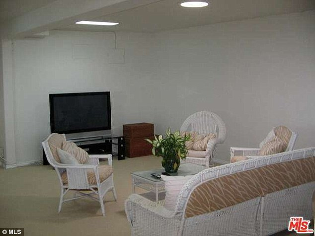 Monochromatic: A minimalist living room is decorated with white, wicker furniture positioned around a flat screen TV