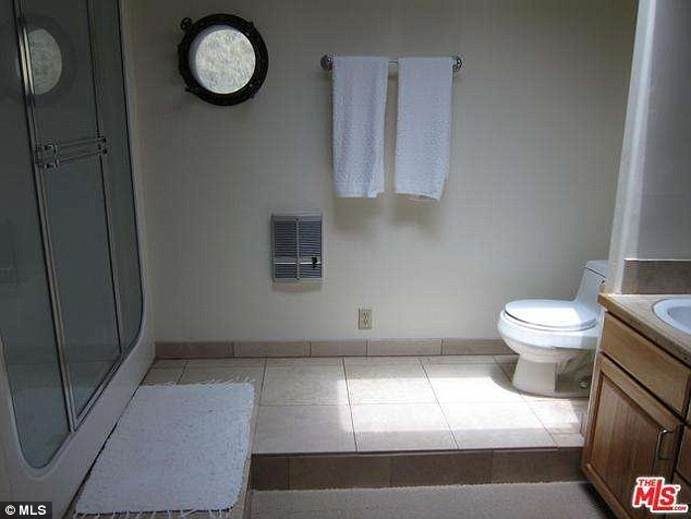 Whimsical: One of the property's four bathrooms features a glass-enclosed shower and is decorated in a nautical theme