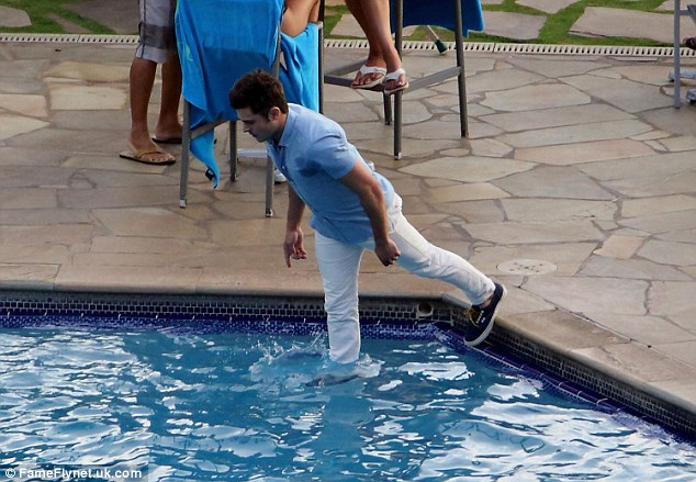 Taking a dip: The Neighbors actor was seen taking a dive into a pool while fully clothed in white slacks and a blue button-down