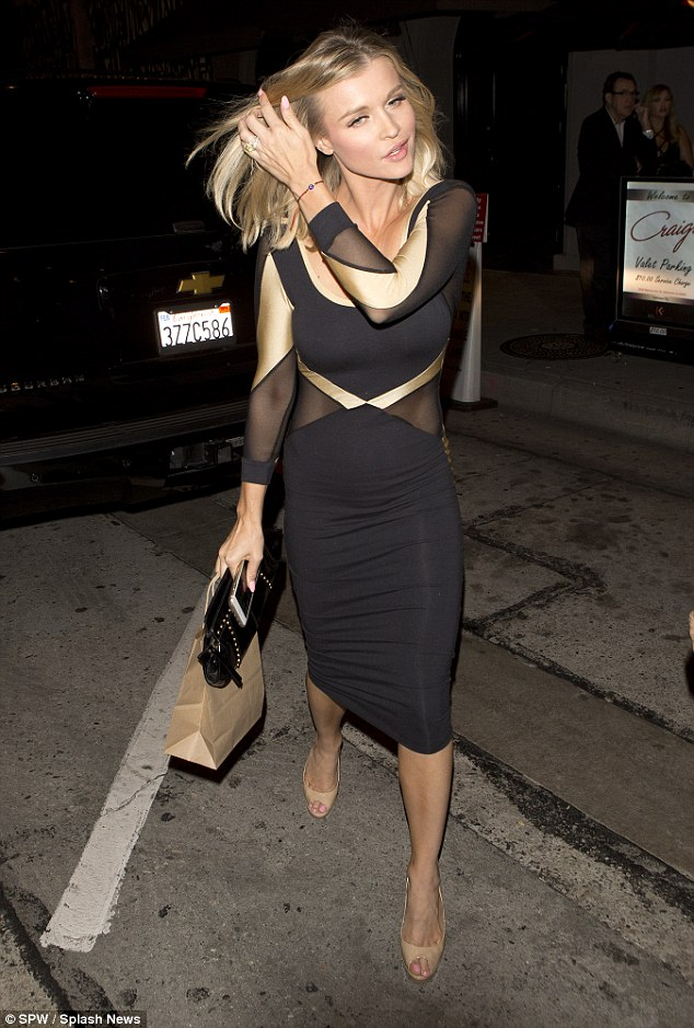 Blonde beauty:Giving extra height to her already long frame, Joanna opted for super high nude heels and she held a black studded clutch bag
