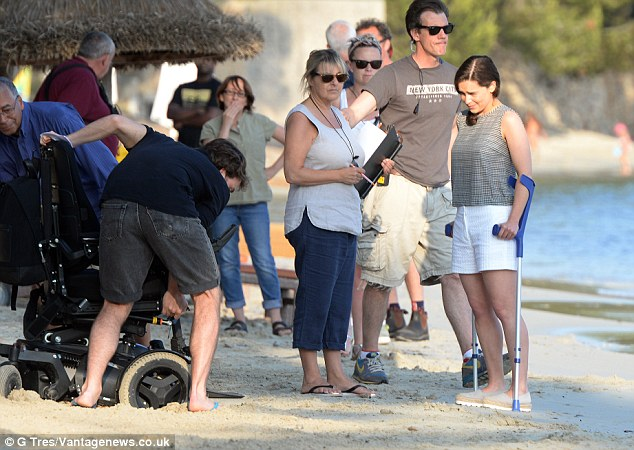 On set: Sam and a crew member bend down to lift a wheelchair out of the sand as a bemused Emilia looks on