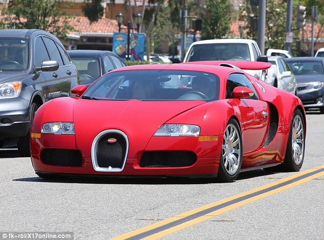 Coordinating: Tyga - who also has a red matte Range Rover - was seen test driving a bright red Bugatti