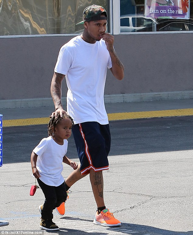 Doting dad: Tyga kept close to his young son as the two walked back to the car after shopping