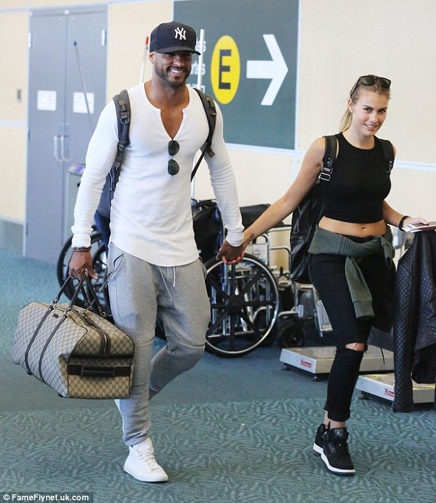 Loved up: Ricky Whittle beamed as he walked through Vancouver airport with his new girlfriend, Sara, on Thursday