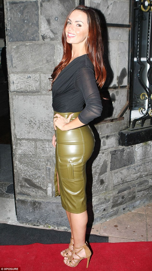 On show: Leaving little to the imagination, she sported a plunging, semi-sheer black top which she matched with an olive green leather-effect skirt, which featured an attention-grabbing slit up the front