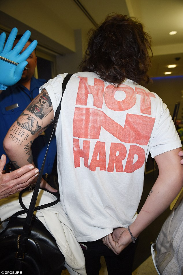 'Hot N Hard': As he turned to make his plane, the Best Song Ever performer - who has been linked to a string of women, including Taylor Swift and Caroline Flack - showed off a cheeky slogan on the reverse...