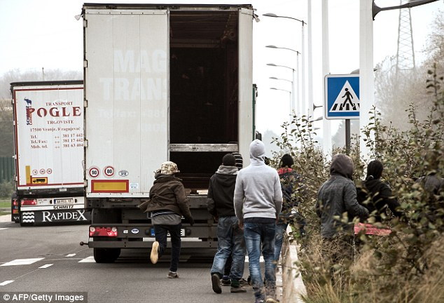 A group of desperate migrants dash after a lorry heading for Britain - as much as £10million worth of fresh fruit and vegetables has been dumped because of migrants breaking into trucks