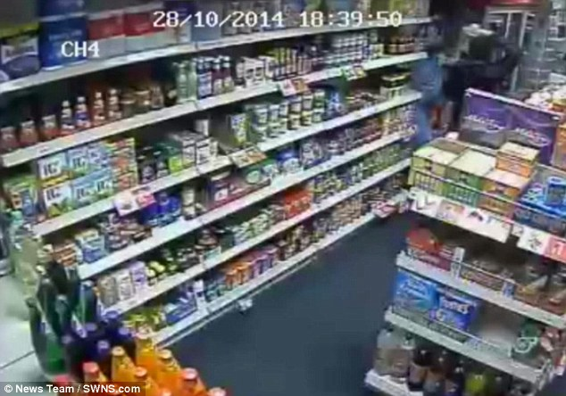 The shop owner can be seen from one angle trying to protect himself behind a card stand after a jar smashes on his head