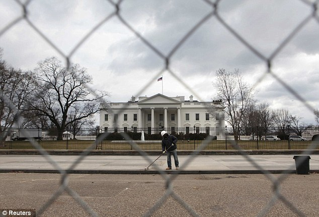 Empty: A worker cleans a barren sidewalk outside the White House in Washington on Saturday, one day after the government stumbled headlong toward wide-ranging spending cuts that threaten to hinder the economic recovery