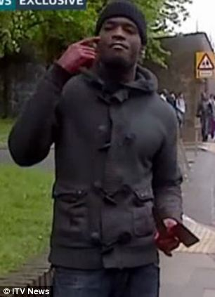 Footage from ITV NEWS showing Woolwich soldier attack . Attacker seen clutching knives , later walking in front of murdered body to his fellow assailant beside crashed car / MUST CREDIT ITV NEWS
