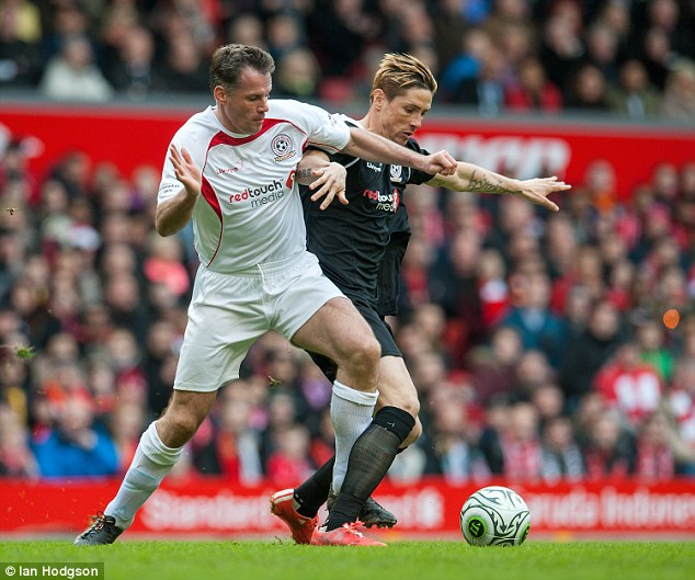 Carragher tussles with Fernando Torres (right) during a Liverpool legends charity match earlier this year