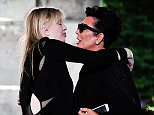 Courtney Love, left, and Kris Jenner, right, engage in a hug as they arrive at the Givenchy men's Spring-Summer 2016 fashion collection presented Friday, June 26, 2015 in Paris, France. (AP Photo/Zacharie Scheurer)