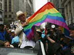 Actor Ian McKellen (C) holds a rainbow flag as he attends as grand marshal during the annual Gay Pride parade in New York June 28, 2015. REUTERS/Eduardo Munoz
