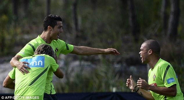 Having fun, Cristiano? Ronaldo fools around with Madrid team-mates Fabio Coentrao (left) and Pepe (right) while training with Portugal