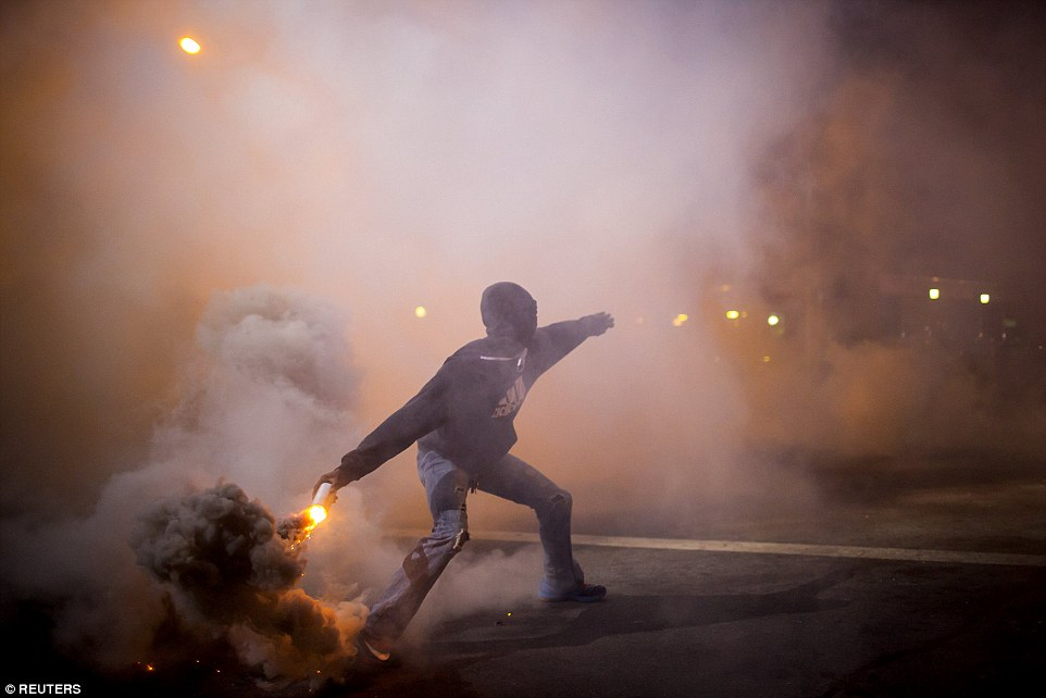 Back and forth: A protester throws a gas canister back at police during clashes at North Ave and Pennsylvania Ave in Baltimore, Maryland last night